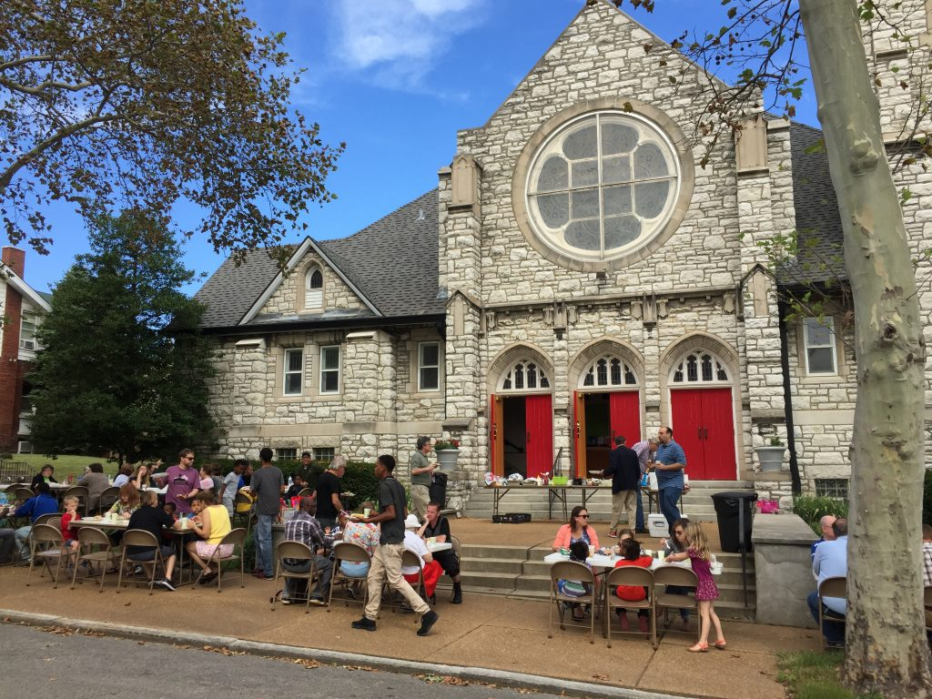 A photo of the congregation eating lunch outside the church on the front steps on a warm, sunny day.